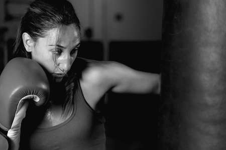 punching bag: Close-up of professional female athlete practicing strokes on punching bag. Black and white