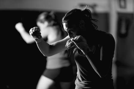 Professional female boxer practicing strokes. Black and white