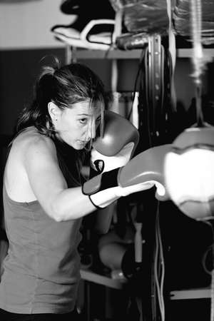 female boxer: Young female boxer practicing strokes, wearing boxing gloves