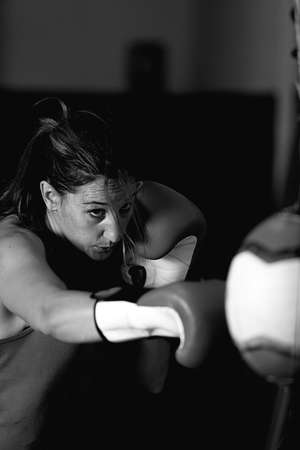 cola mujer: Aggressive female athlete boxing in gym, wearing boxing gloves. Black and white