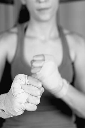 female boxer: Close-up of young female boxer with tied up fists. Unrecognizable