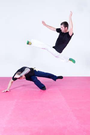 men exercising: Two men exercising capoeira in gym-hall