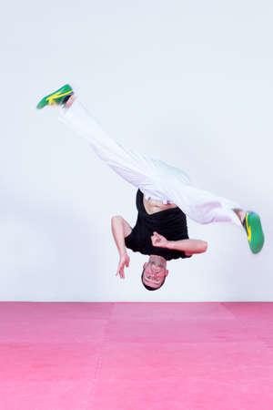 cabeza abajo: Salto del hombre joven, bailando capoeira. Al revés