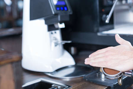 bartenders: Bartenders hand with holder, grinding coffee machine on background. Unrecognizable