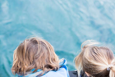Back view of two children looking down at water, from above. unrecognizable Stock Photo