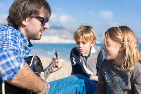 three day beard: Children and father singing song on beach while he playin guitar Stock Photo
