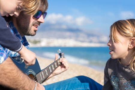 three day beard: Close-up of two children and father singing song on beach while playing guitar
