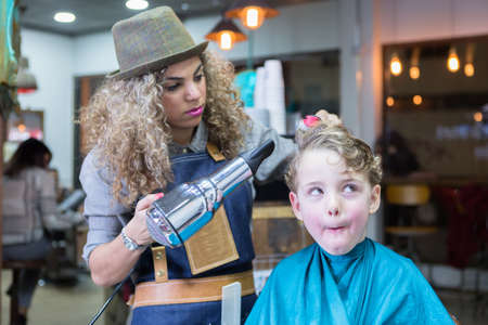 blow dry: Little boy making faces in barber chair while woman blowing dry his hair
