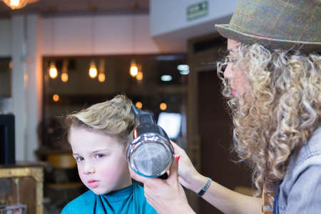 horizontal haircut: Portrait of boy gets his hair blow-dry, looking seriously Stock Photo