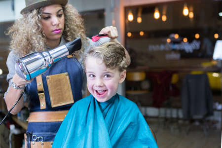 haircutter: Little boy smiling while woman blowing dry his hair