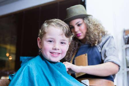 horizontal haircut: Boy looking at camera and smiling in barber shop