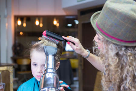 horizontal haircut: Hairdresser blowing dry boy hair using brush and hairdryer Stock Photo