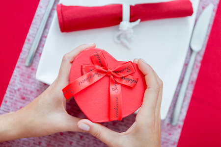napkin ring: Close-up of woman hands holding present heart-shaped box. Red napkin with ceramic napkin ring on background. Unrecognizable