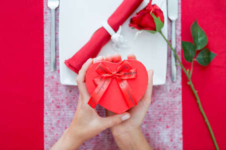 romantic date: Woman hands holding heart-shaped present box. Romantic decorated table on background. Unrecognizable. Stock Photo
