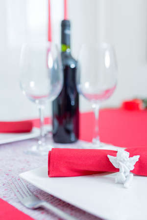 napkin ring: Close-up of ceramic napkin ring in form of angel against unfocused wine and glasses on background. Saint Valentines day.