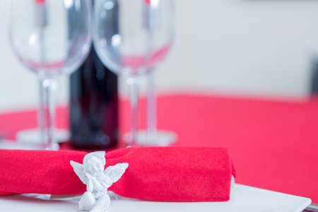 napkin ring: Red napkin with ceramic napkin ring in form of angel. Close-up