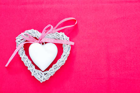 copy sapce: Handmade white wicker heart with checked ribbon. Pink background Stock Photo