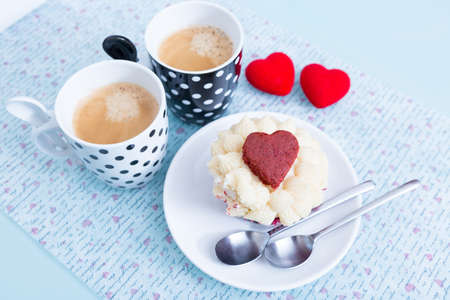 saint valentines: Composition of two cups of coffee and a cupcake on saucer on decorated table. Saint Valentines Day. Stock Photo