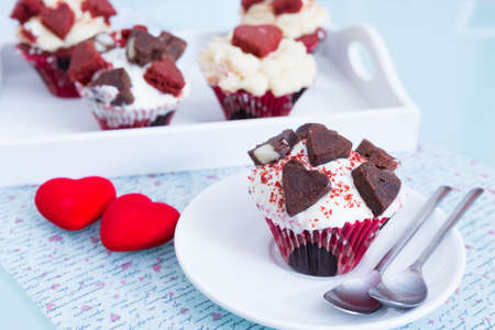 saint valentines: Several cupcakes for Saint Valentines day on white tray. Two red decorative hearts on table