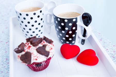 saint valentines: Saint Valentines cupcake, cups of coffee and two red hearts on white wooden tray Stock Photo
