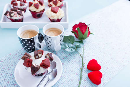 saint valentine's day: Two cups of coffee and handmade cupcake near red rose and decorative hearts. Saint Valentines day. Copy space area
