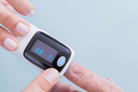 puls: Female medic and old woman patient using medical device called finger pulse oximeter.