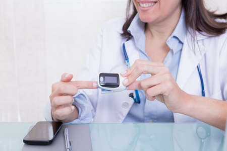 Junge Mediziner zeigt Finger-Pulsoximeter. Standard-Bild