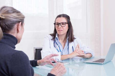 medico con paciente: Mujer de edad avanzada del paciente hablar con el médico de la mujer en la sala de consulta. Foto de archivo