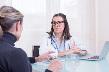 Old woman patient talking to female doctor in consulting room.