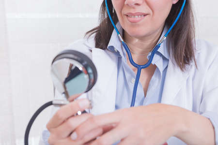 aneroid: Smiling young female medic looking at manometer while measuring blood pressure. Stock Photo