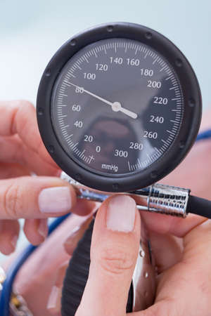 manometer: Womans hands holding manometer. Stock Photo
