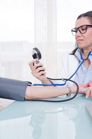 manometer: Young female medic measuring old patient blood pressure and looking at manometer. Close-up