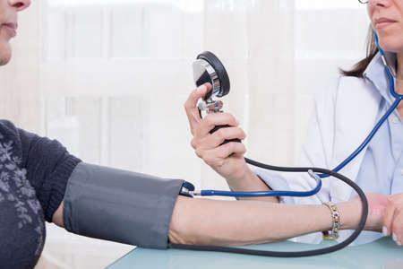 sphygmomanometer: Female doctor using aneroid sphygmomanometer and stethoscope for measuring patients blood pressure. Close-up. Unrecognizable