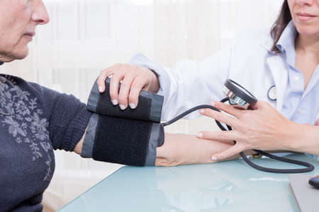 put pressure: Female doctor putting sphygmomanometer on old patient arm Close-up. Unrecognizable
