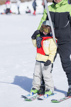 stirrup: Unrecognizable parent and his son on  stirrup going up to ski Stock Photo