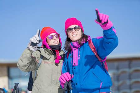 ropa de invierno: Dos mujeres adultas en ropa de invierno apuntando a algo con el dedo Foto de archivo