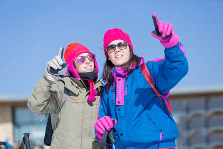 winter clothes: Two adult women in winter clothes pointing at something with finger