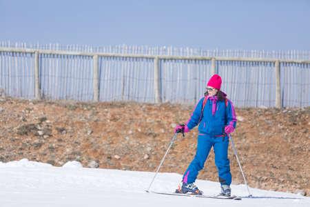 ropa de invierno: mujer adulta en ropa de invierno brillantes de pie mientras llevaba los esqu�s