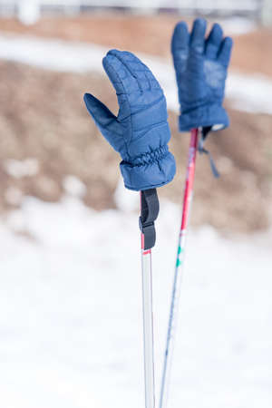 winter gloves: Close-up of two blue winter gloves hanging on ski poles. Bokeh. Stock Photo