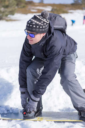 binding: Adult man in sunglasses and hat putting on his snowboard boots in binding while standing up Stock Photo