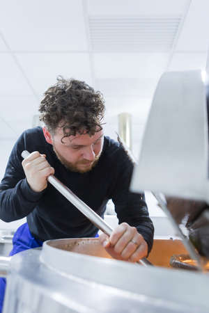 elaboration: Serious man with curly hair looking down while stirring beer with metal bar Stock Photo