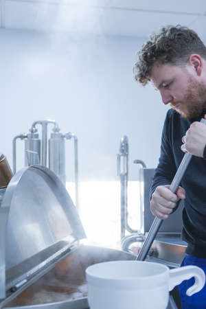 side bar: Side view of man stirring beer with metal bar on a craft beer elaboration process Stock Photo