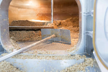 elaboration: View on metal open furnace with dried malt seeds and shovel inside. Craft beer elaboration