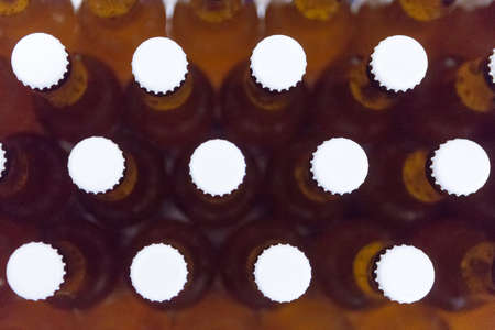 lids: Close-up of full beer bottles with white lids. From above. Useful as a background