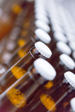 lids: Close-up of lines of beer bottles with white lids