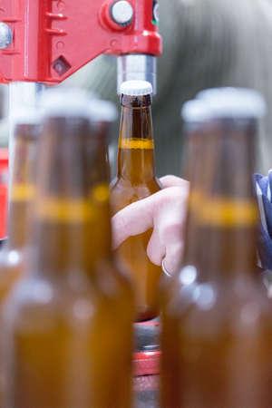 elaboration: Unrecognizable man holding glass bottle. Beer bottles on foreground