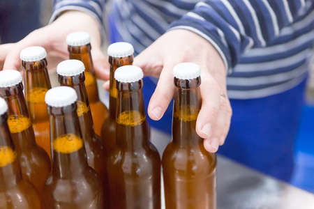 elaboration: Close-up of man taking full beer bottles on a craft beer elaboration process. Unrecognizable