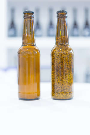 brown bottles: Close-up of brown bottles full of wheat and beer on white table Stock Photo