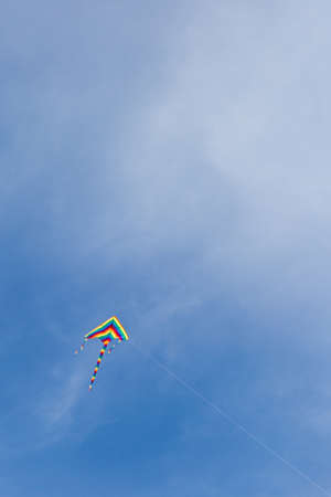 from below: Bright kite with rope flying in blue sky. From below. Copy space Stock Photo