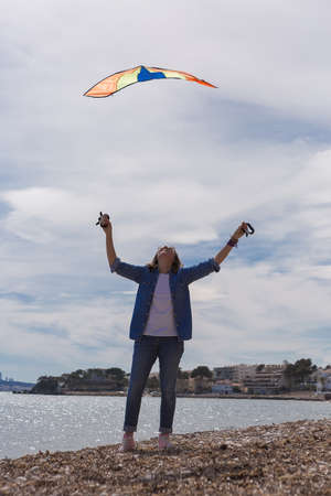outstretched arms: Adult woman on coastline holding colorful flying kite while looking up with outstretched arms
